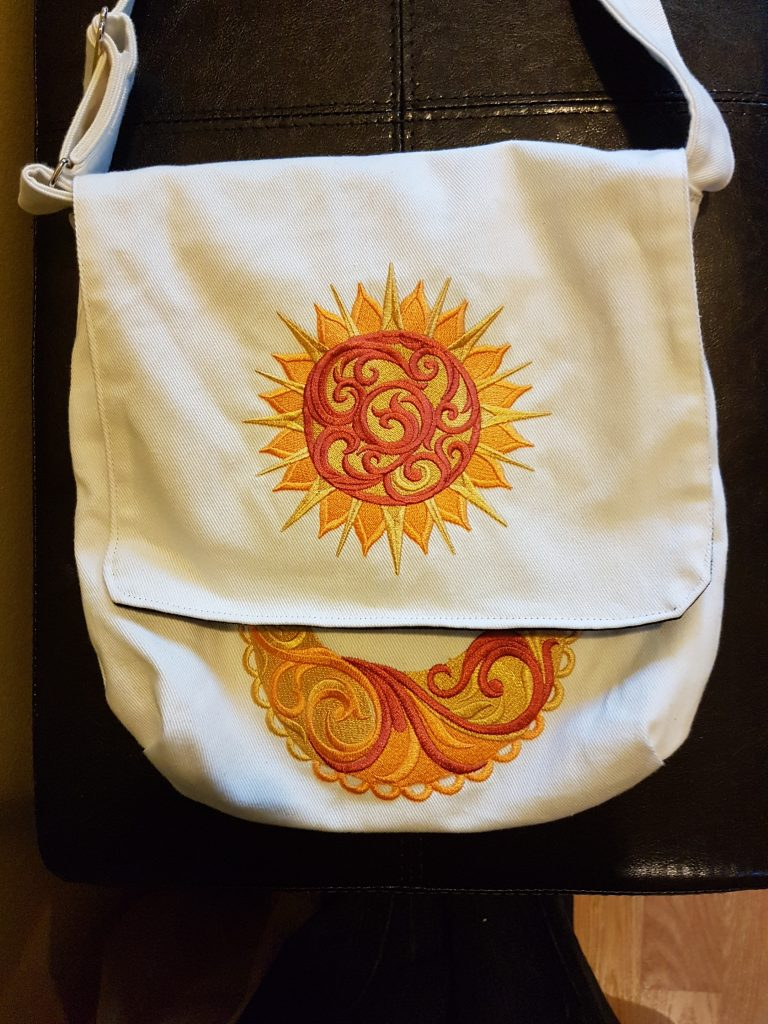 A white canvas bag with a sunburst embroidered on it in red, orange, and gold thread.