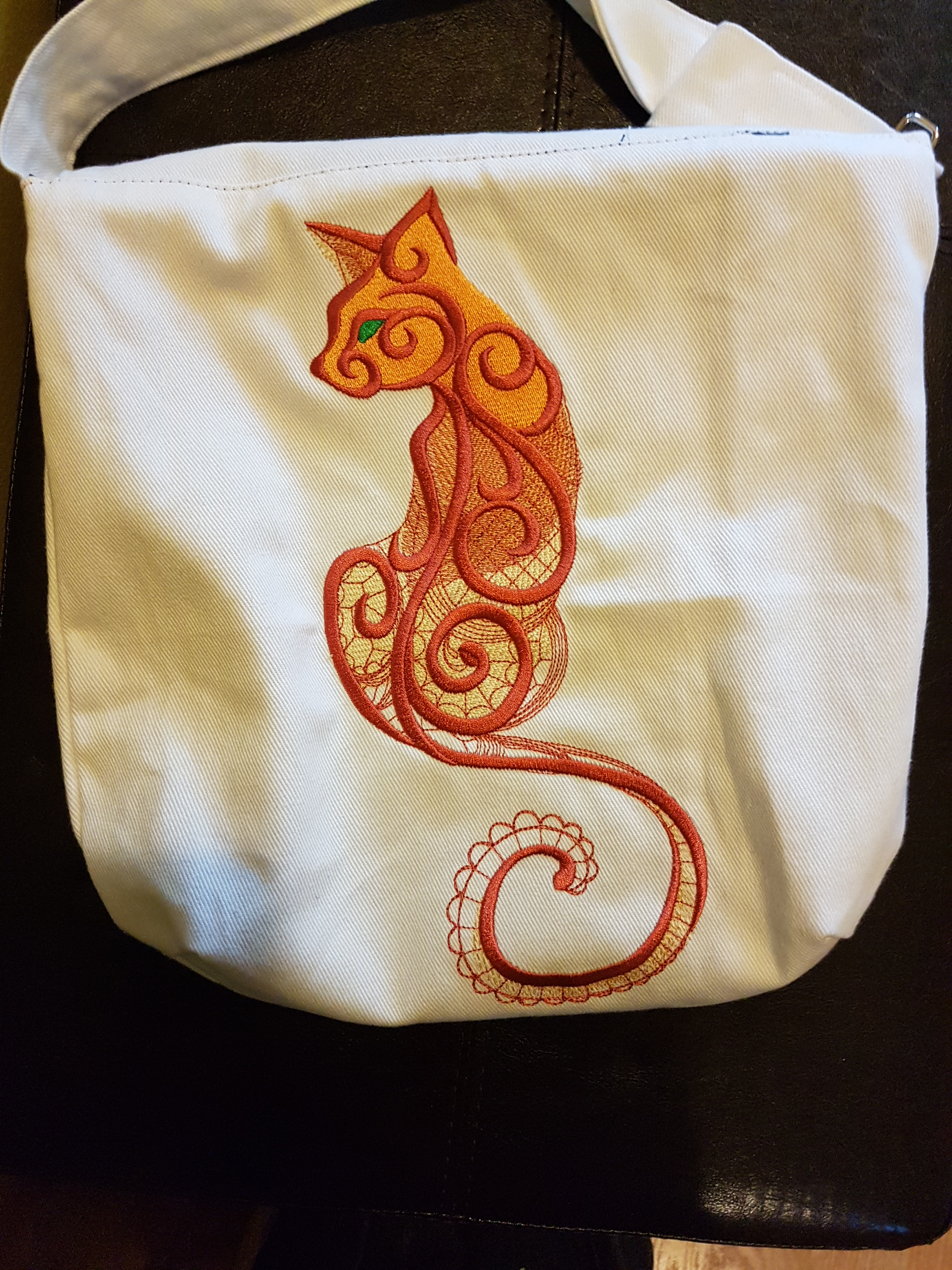 The back of the white canvas bag shows a fully-grown cat embroidered with gold, orange, and red thread. The cat's eyes are embroidered in green thread.