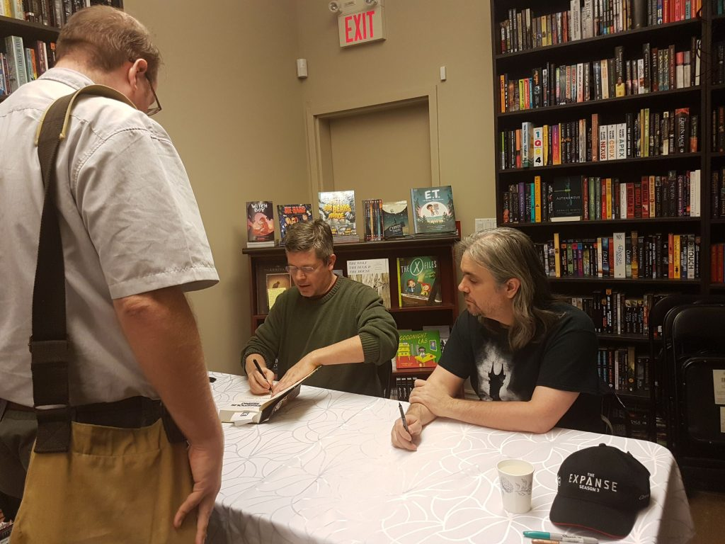 Daniel Abraham and Ty Franck sign my husband's copy of Persepolis Rising.