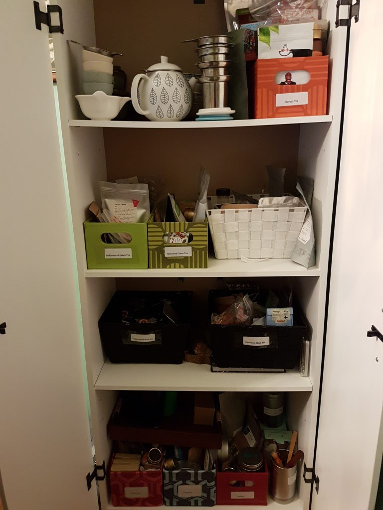 A white plywood cabinet with four shelves inside. Each shelf contains several boxes of loose-leaf tea, and each box belongs to its own category.