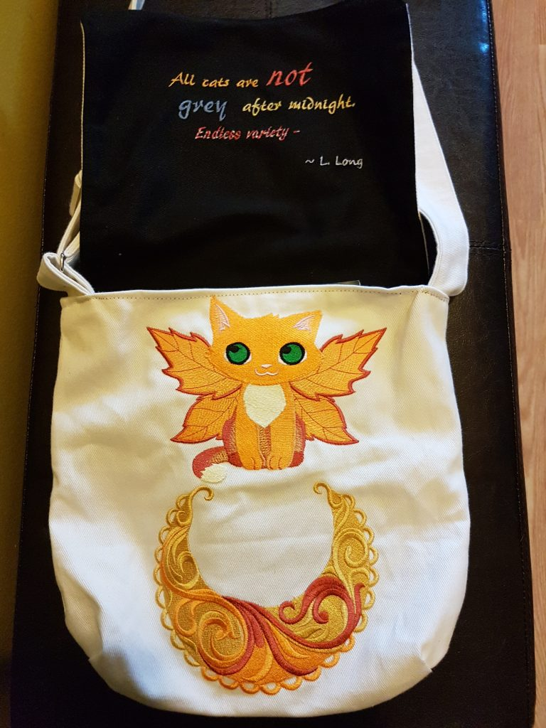 The white canvas bag opens up to reveal an interior lined with black fabric. The flap with the sunburst on the front opens up to reveal an embroidered quotation from Lazarus Long. Immediately underneath the front flap is more white fabric with a kitten and a sunburst crescent embroidered upon it, both with red, orange, and gold thread. The kitten's eyes are embroidered in green thread.