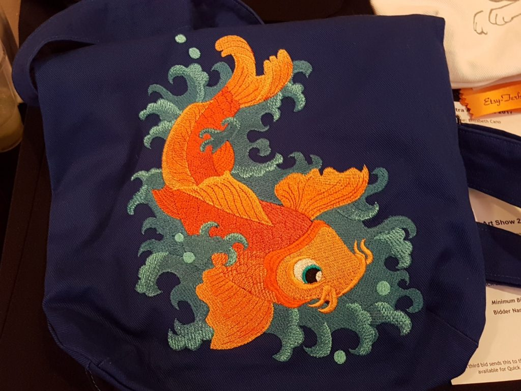 A navy blue canvas bag embroidered with a koi fish splashing in water. The koi is embroidered in varying shades of orange and the waves are embroidered in varying shades of blue.