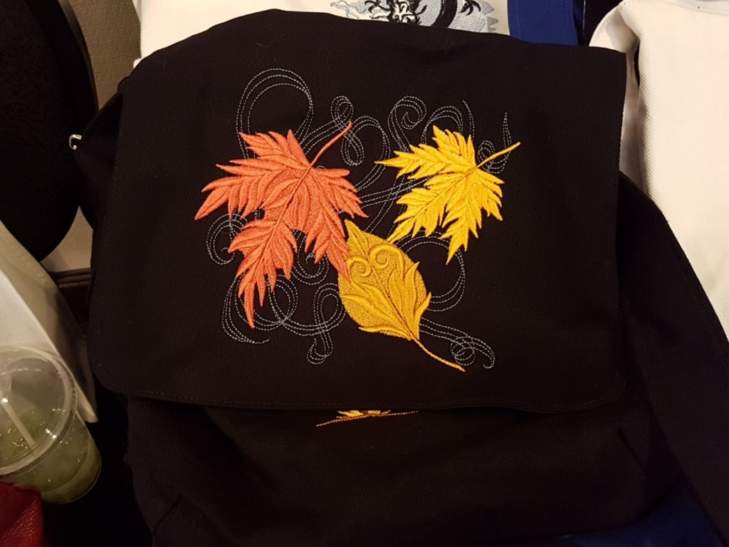 A black canvas bag embroidered with falling leaves in a variety of colours.