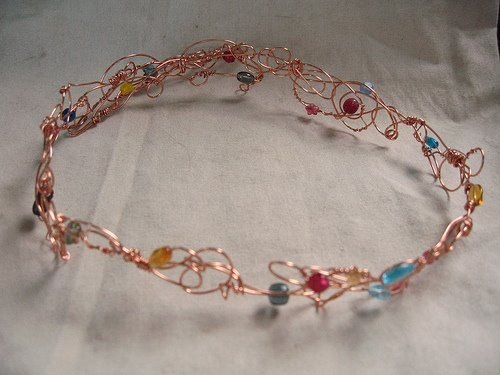 A photo of the Campbell tiara, designed by Amanda Downum. It is a circlet of copper wire and glass beads that the winner wears. It's passed on from one winner to the next.